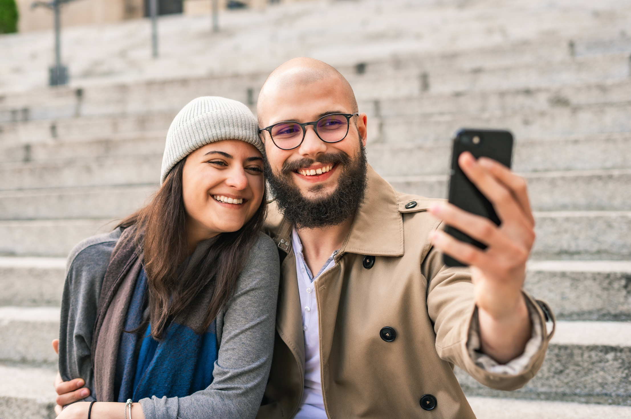 Smiling young couple taking selfie with smartphone